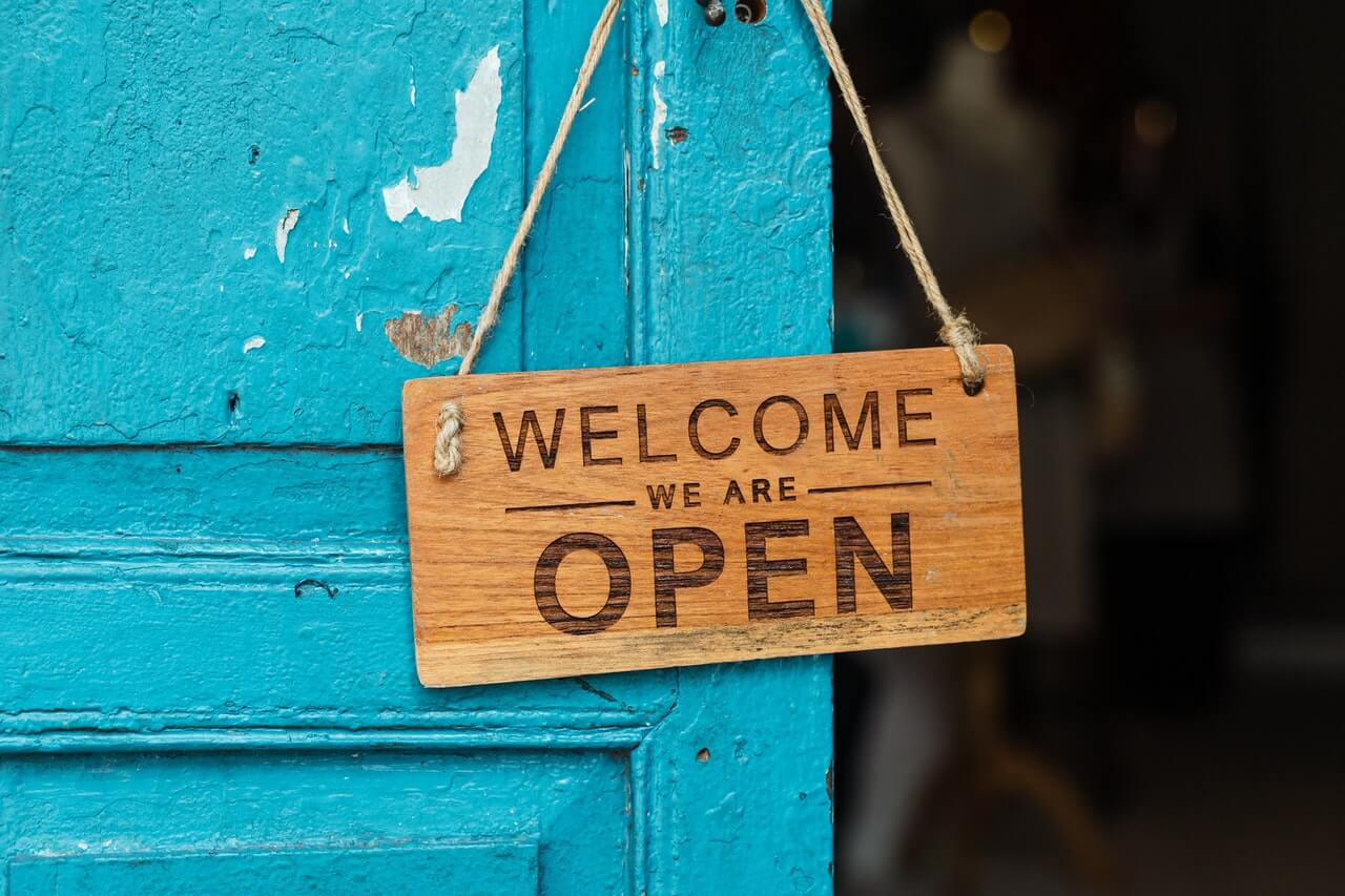 Photo of a Welcome We Are Open sign on the door. Used in TVIA post #4 Let's Get At It!